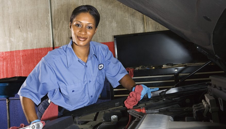 Auto mechanic posing next to car