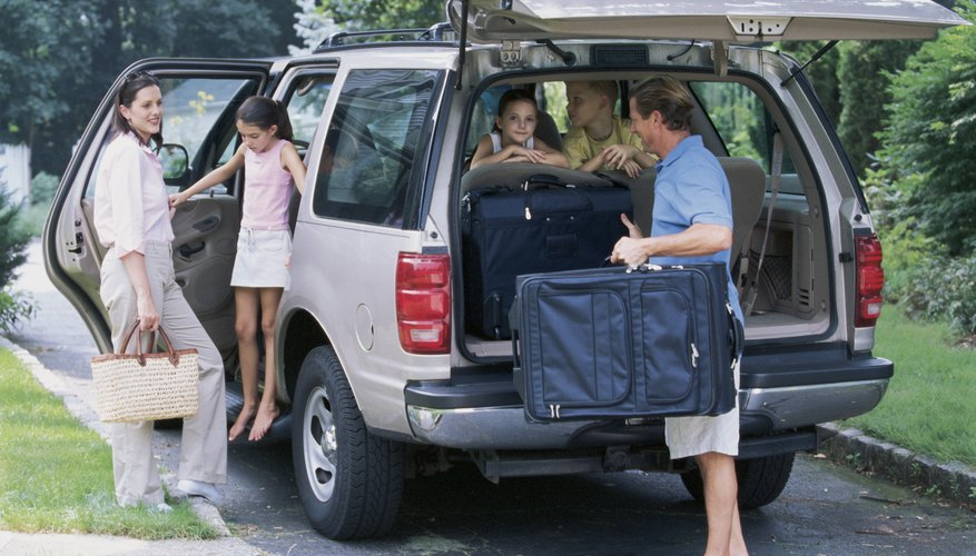 Family packing suitcases into SUV