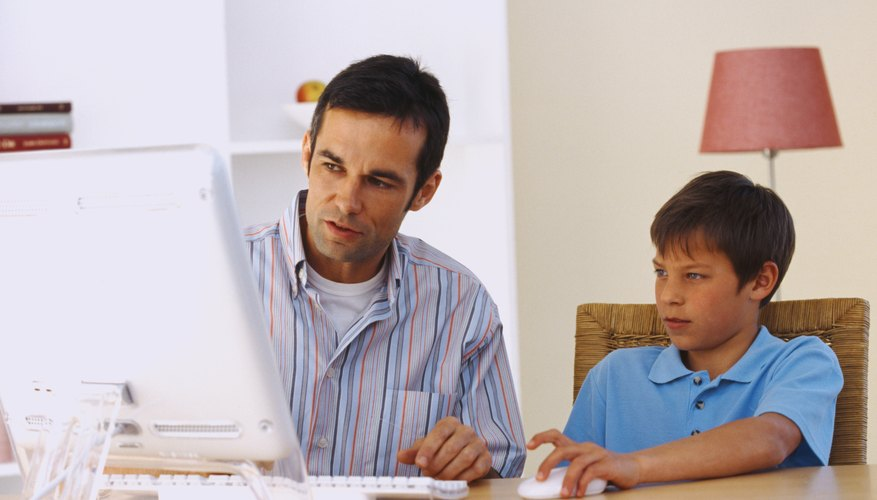 Mid adult man sitting at a table and working on a computer with his son (10-12)