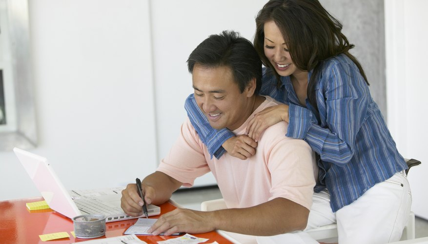 Woman stands over her husband as he writes a check