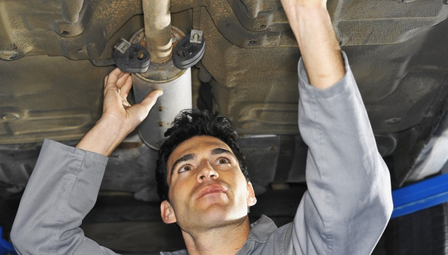 Low angle view of a male mechanic fixing an exhaust pipe on a car