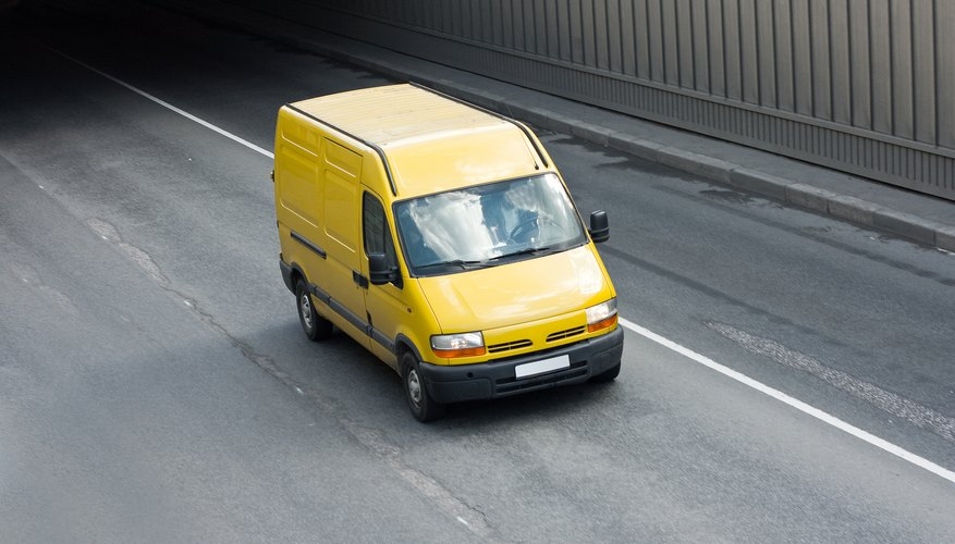 Yellow cargo van on road.