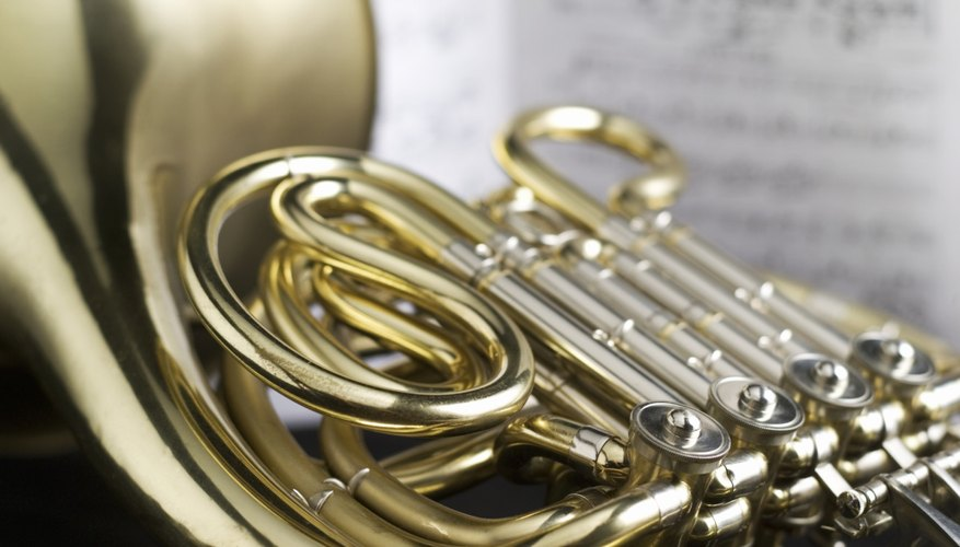 Repair a French horn by restringing the valves.