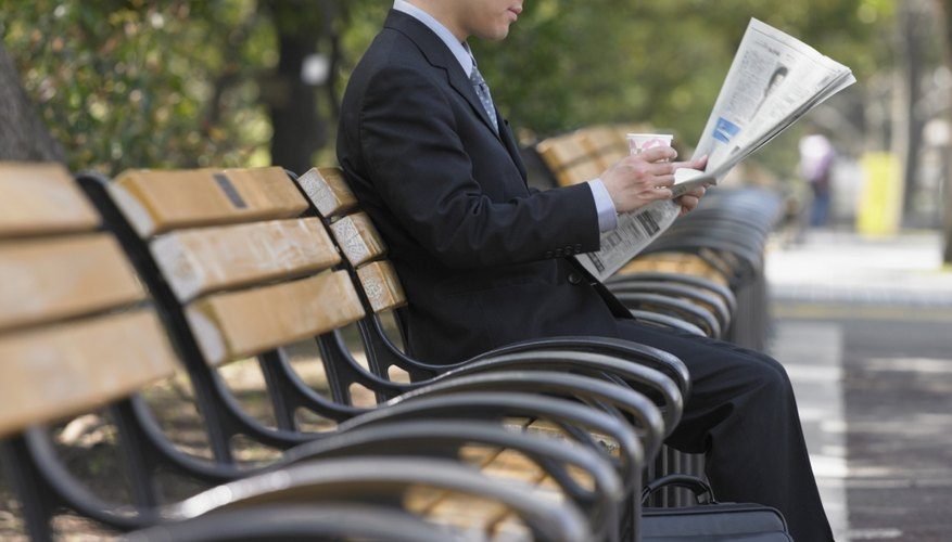 Asian businessman reading newspaper on park bench