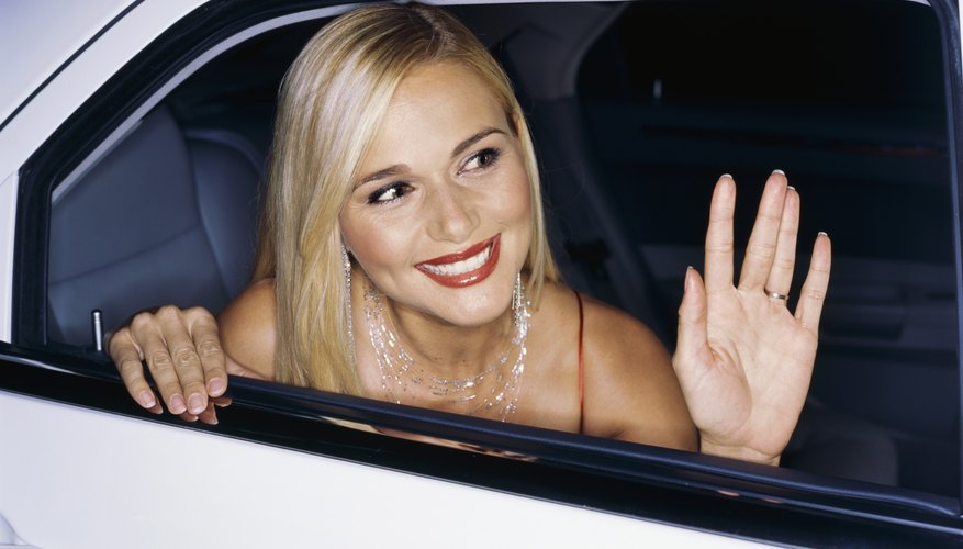 A star waves from the window of a limousine.