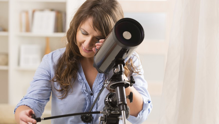 Young woman using a telescope.