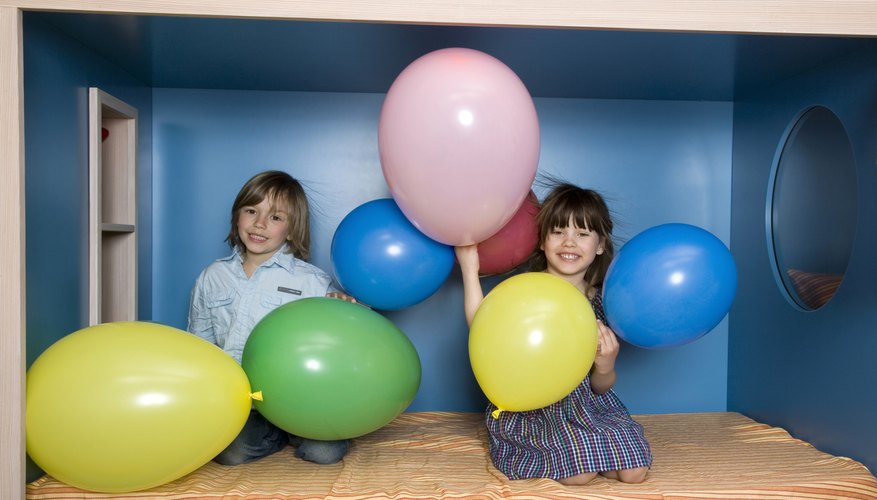 A boy and girl playing with balloons.