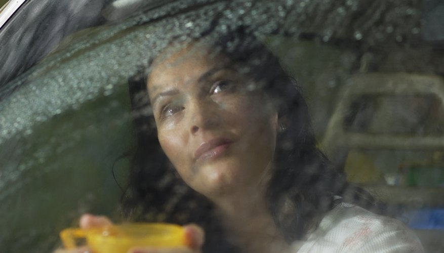 Woman looks out car window