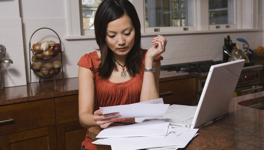 Woman looking at paperwork next to laptop