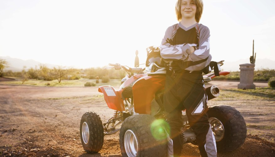 Boy posing by ATV, Arizona