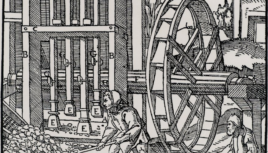 Medieval miners grinding mineral ore at a mill.