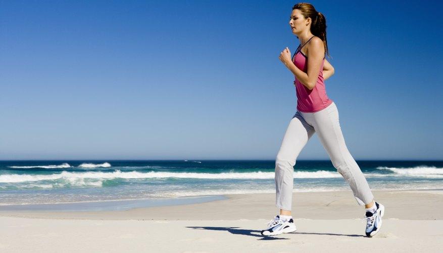 A woman runs along a shore.