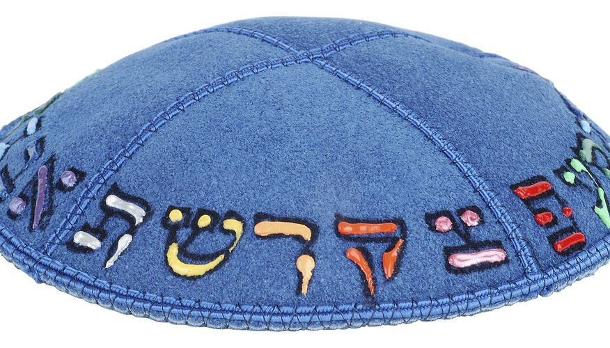 A suede kippah with the Hebrew alphabet painted on it.