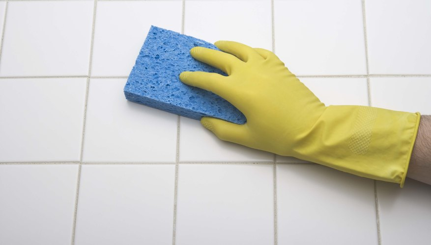A gloved hand is cleaning the kitchen floor.