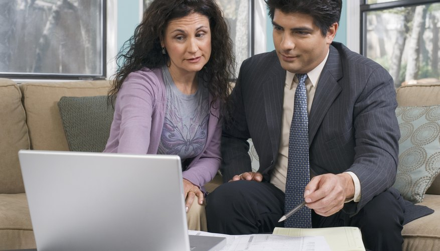 Two people are looking at their laptop.