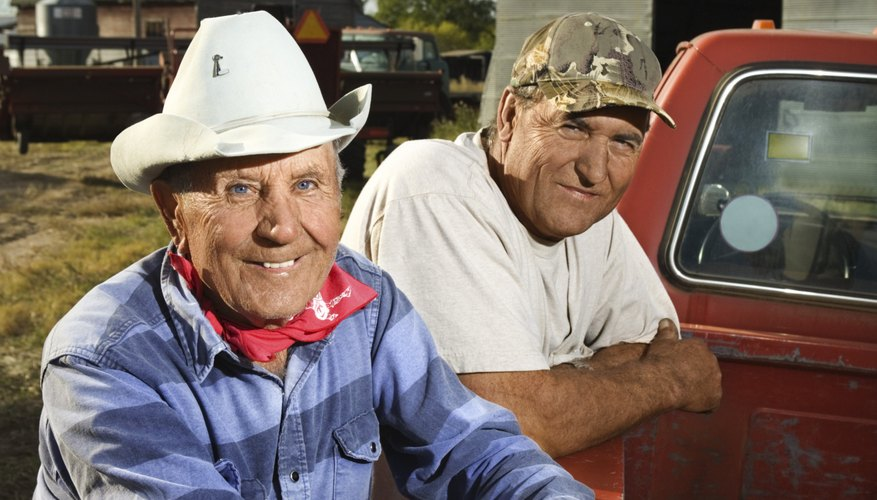 Men leaning on pickup truck smiling
