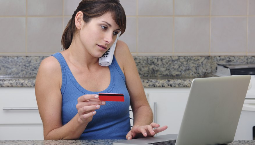 A young woman in her kitchen is on the phone with her credit card in hand and another hand on the keyboard of a laptop computer.