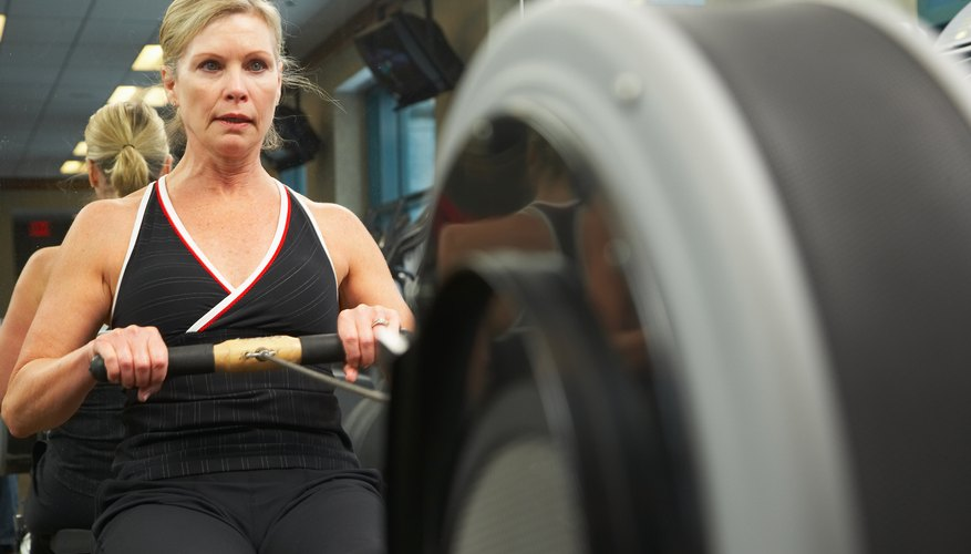 A woman exercises on a rowing machine.
