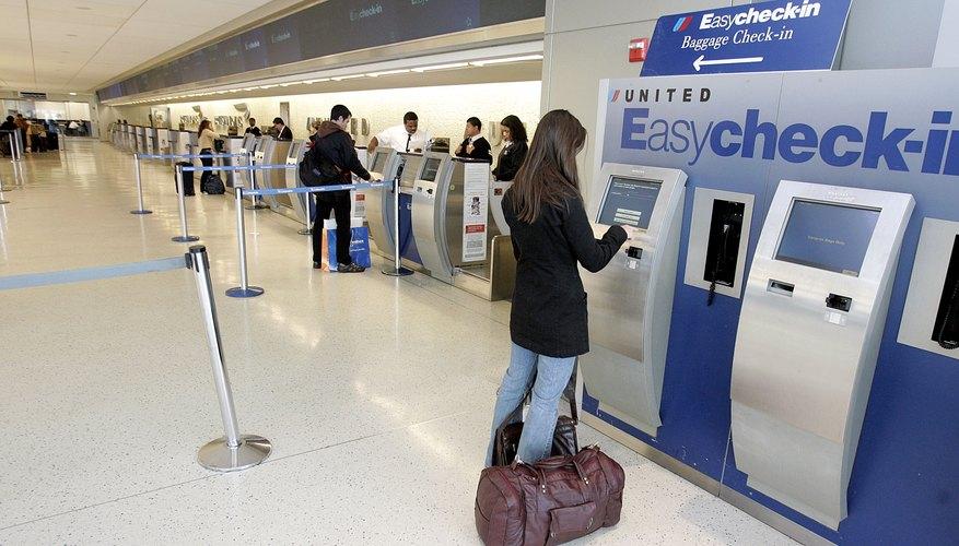 Una mujer utilizando la terminal EasyCheck-in de United en el aeropuerto internacional JFK en Nueva York.