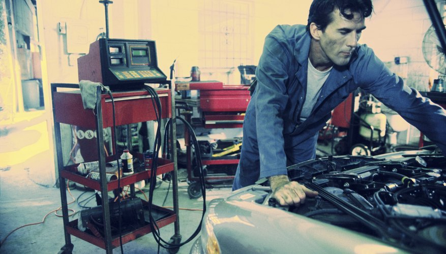 Auto mechanic working over the engine bay of a car