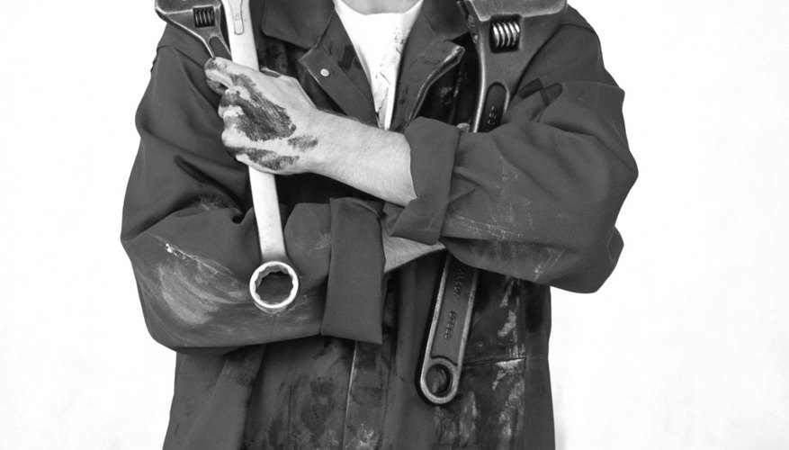 Greasy mechanic holding wrenches