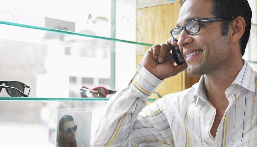 Man using mobile phone while standing by window display in eyeglass store