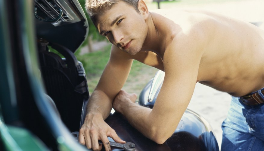 Side view of a young man repairing a car