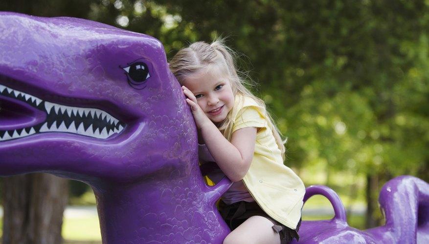 A girl sits atop a spring rider dinosaur.