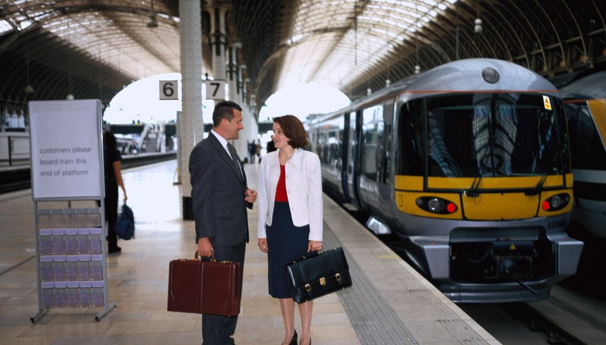 Business man and woman talking as a train arrives at the platform.