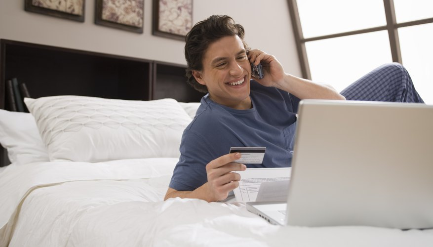 Man holding a credit card in front of a computer while on the phone.