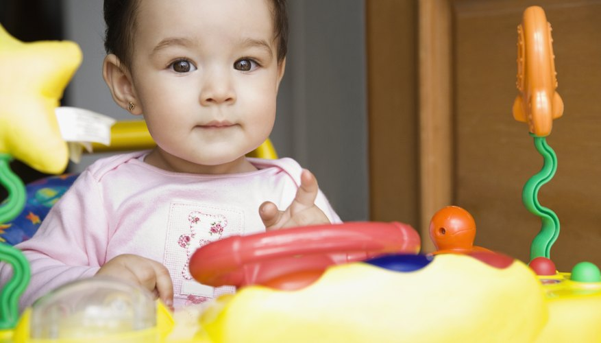 A baby girl sitting in a colorful activity chair.