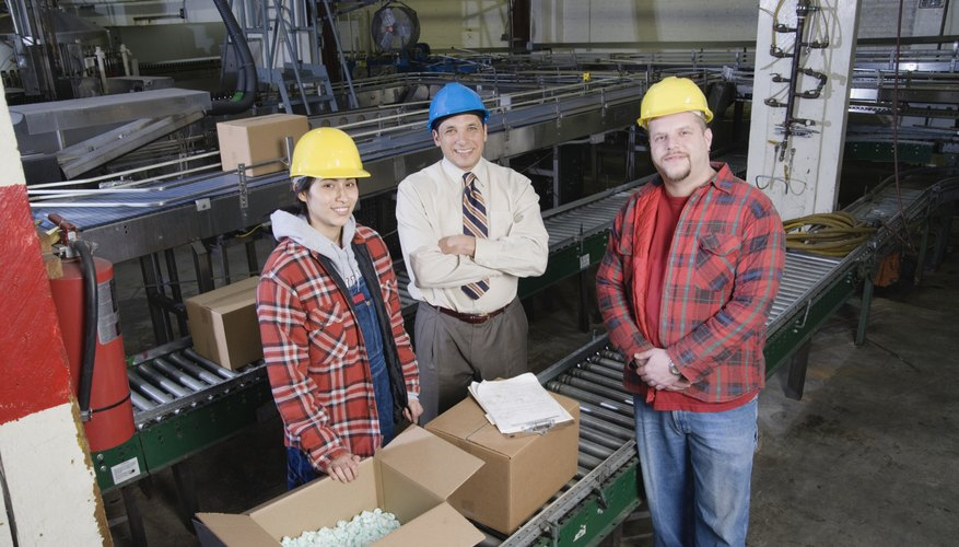 Three people in warehouse looking at camera