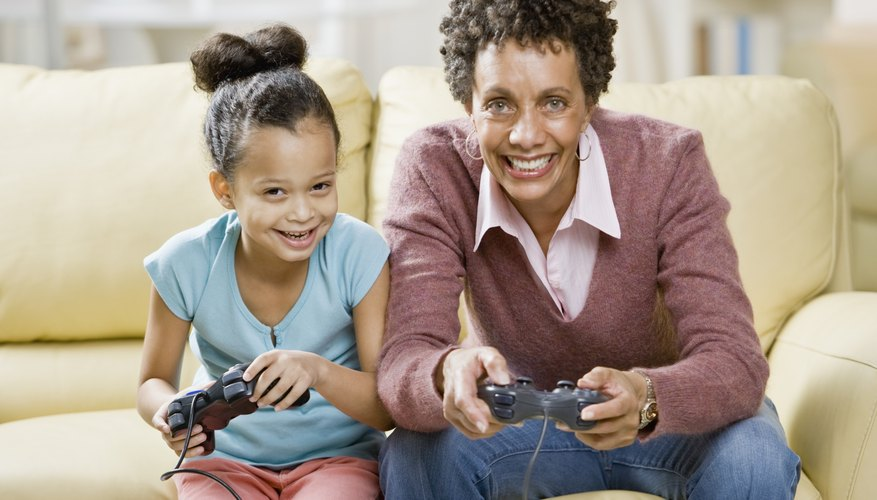 Mother and daughter holding Playstation controllers and sitting on a couch.