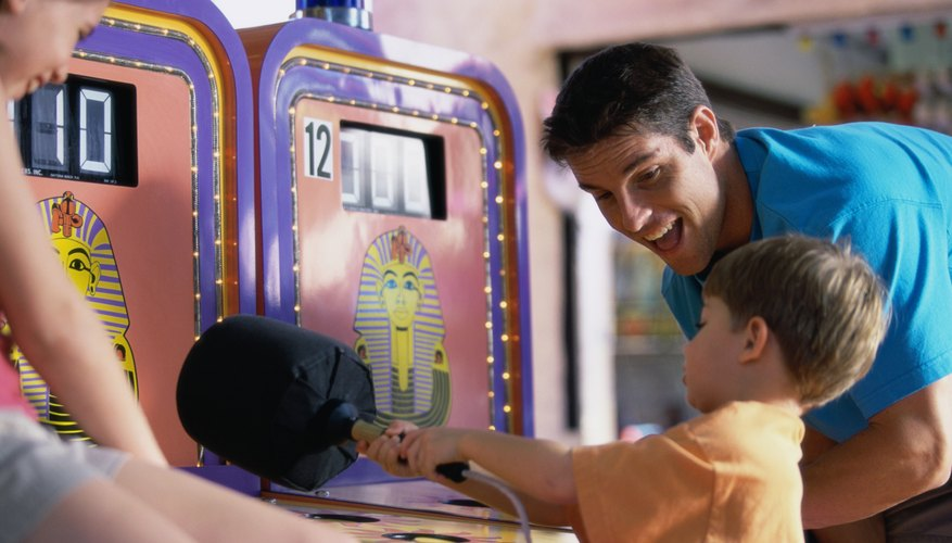 A young boy playing in an arcade.