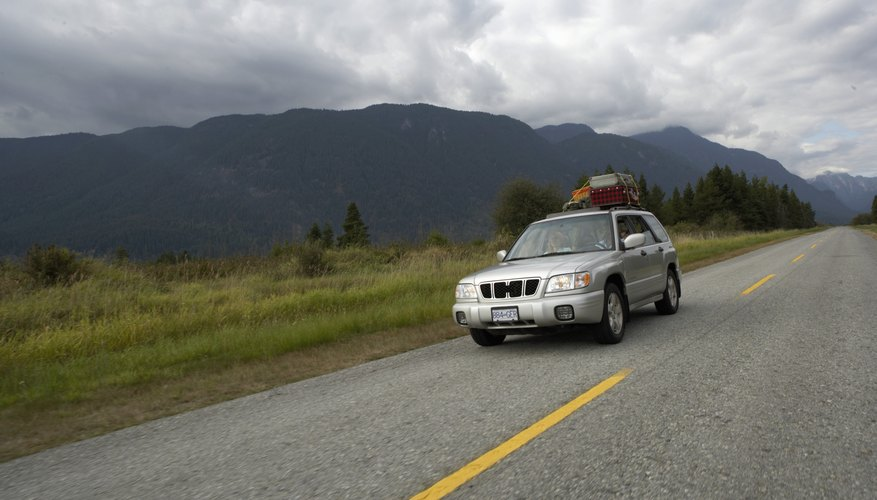 Canada, British Columbia, Pitt Meadows, couple driving sports utility vehicle along rural road