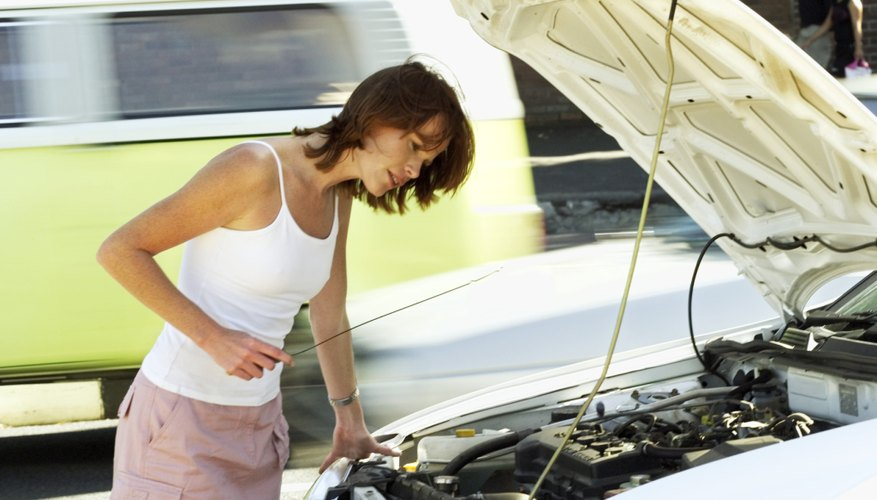 woman checking an oil dipstick
