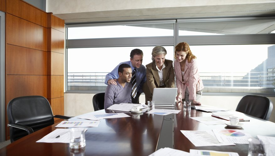 Business colleagues looking at laptop in meeting room, smiling