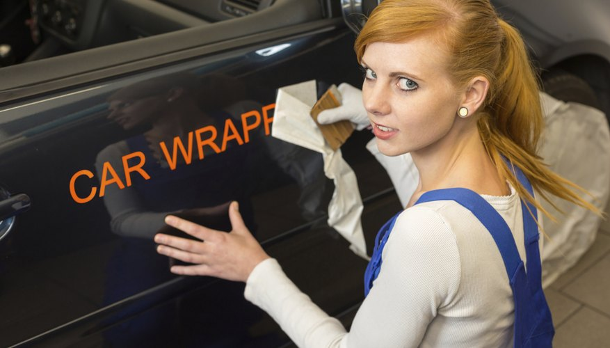 Worker affixes car wrapping foil for advertisement on vehicle
