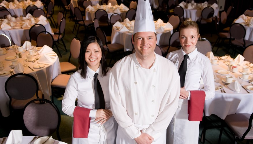 Chef and two servers posing in banquet hall