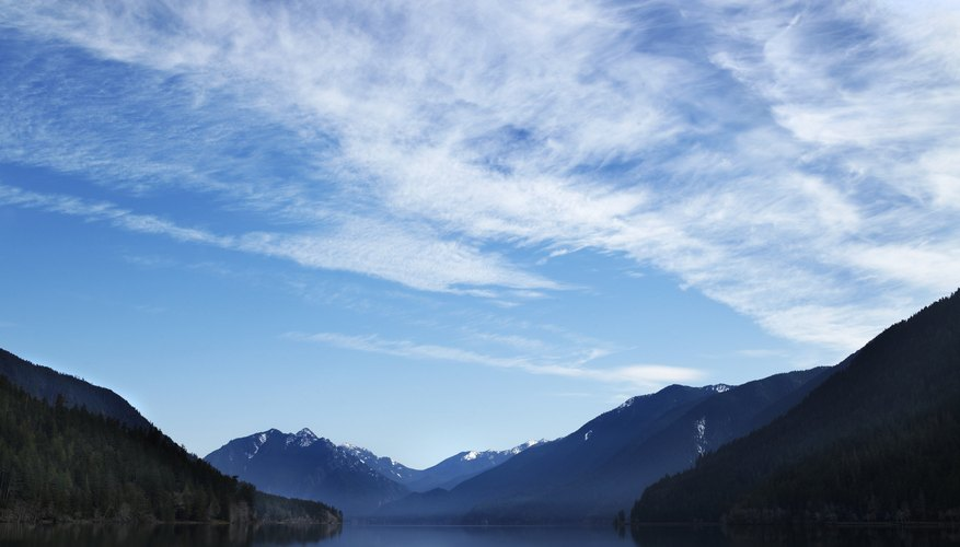 Clouds in the blue sky hovering over a lake in the mountains.
