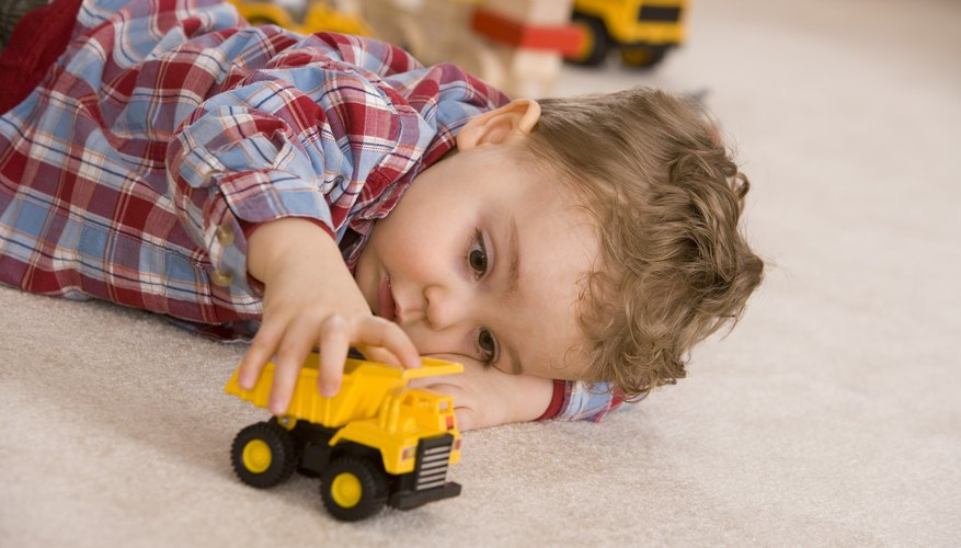 Young boy playing with yellow toy car.