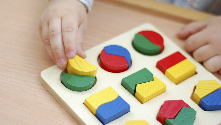 A toddler playing with a colorful shapes puzzle.