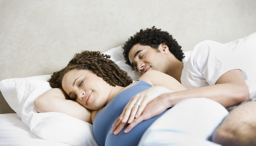 Young pregnant woman sleeping beside her husband in bed.