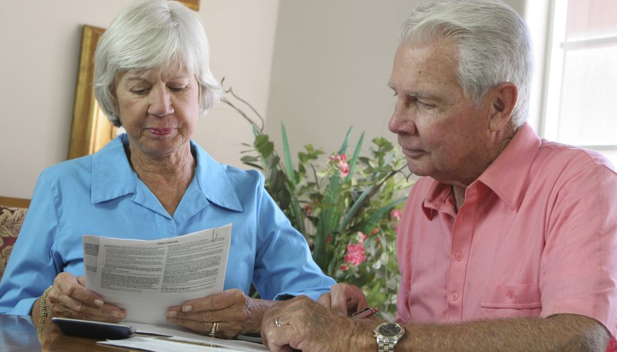 A senior couple reviews paperwork together in their living room