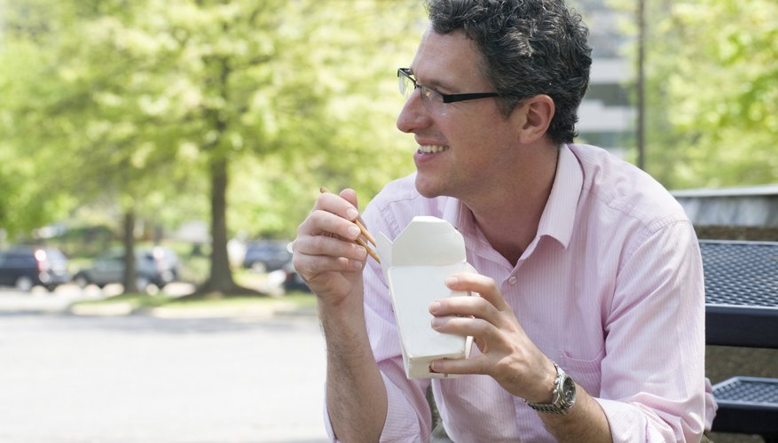 Mature businessman enjoys Chinese carry out for his lunch