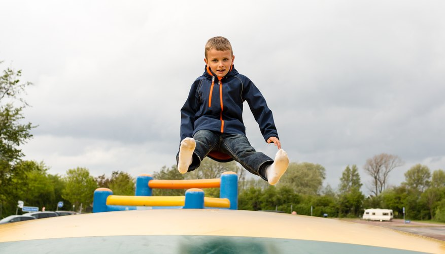 A young boy is bouncing on a trampoline.