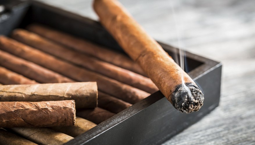 Burning cigar with smoke on old humidor