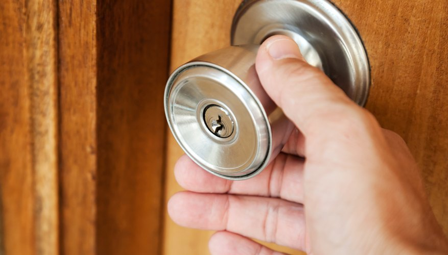 A close-up of a man turning a door knob on a wooden door.