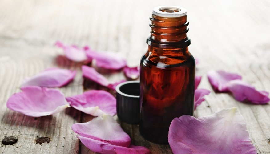 Essential rose oil surrounded by rose petals
