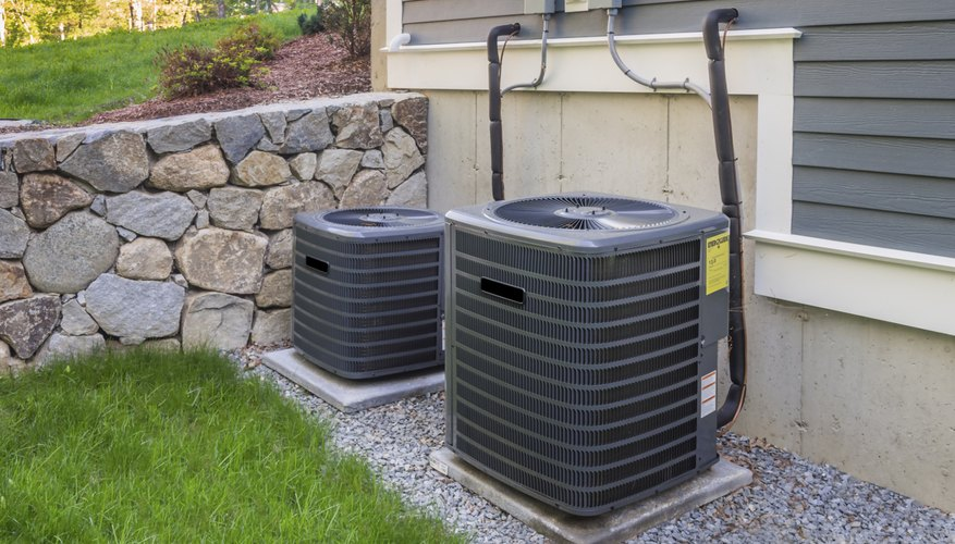 Central air conditioning units in place in the backyard of a home.